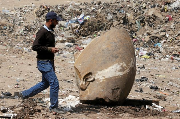 A man passes by what appears to be the head of the unearthed
