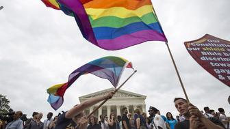 Supporters of gay marriage wave the rainbow flag after the U.S. Supreme Court ruled on Friday that the U.S. Constitution provides same-sex couples the right to marry at the Supreme Court in Washington June 26, 2015. The court ruled 5-4 that the Constitution's guarantees of due process and equal protection under the law mean that states cannot ban same-sex marriages. With the ruling, gay marriage will become legal in all 50 states.    REUTERS/Joshua Roberts