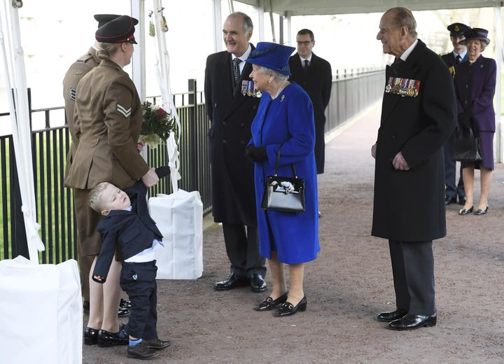 Two-year-old Alfie Lun is held by his mother as Britain's Queen Elizabeth II arrives to unveil The Iraq and Afghanistan memorial at Victoria Embankment Gardens in central London on March 9, 2017.