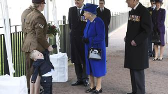 Two year old Alfie Lun is held by his mother as Britain's Queen Elizabeth II arrives to unveil The Iraq and Afghanistan memorial at Victoria Embankment Gardens in central London on March 9, 2017. The preceding 'Service of Dedication' honoured the service and duty of both the UK Armed Forces and civilians in the Gulf region, Iraq and Afghanistan, and those who supported them back home, from 1990-2015 / AFP PHOTO / POOL / Toby Melville        (Photo credit should read TOBY MELVILLE/AFP/Getty Images)