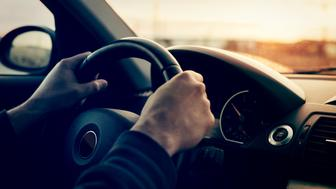 Driving a car in sunny day - focus on steering weel
