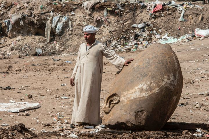 An Egyptian worker stands next to the head of a massive statue that may portray Ramses II on March 9, 2017