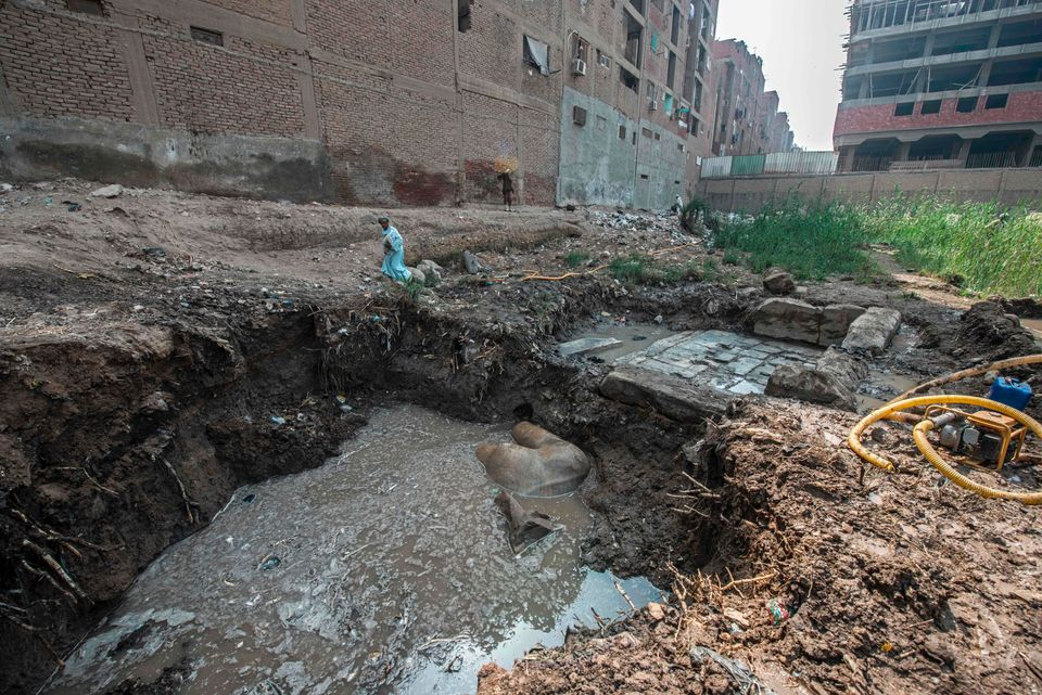 An Egyptian man walks past the site of a new discovery by a team of German and Egyptian archeologists in Cairo's Matariya dis