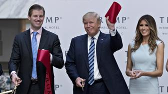 Donald Trump, 2016 Republican presidential nominee, center, holds a piece of ribbon next to his wife Melania Trump, right, and his son Eric Trump during the grand opening ceremony of the Trump International Hotel in Washington, D.C., U.S., on Wednesday, Oct. 26, 2016. The Trump Organization has eight hotels in the U.S. and seven in other countries. The Trump International Hotel Washington, D.C. is housed in the 1899 Romanesque Revival-style Old Post Office on Pennsylvania Avenue. Photographer: Andrew Harrer/Bloomberg via Getty Images