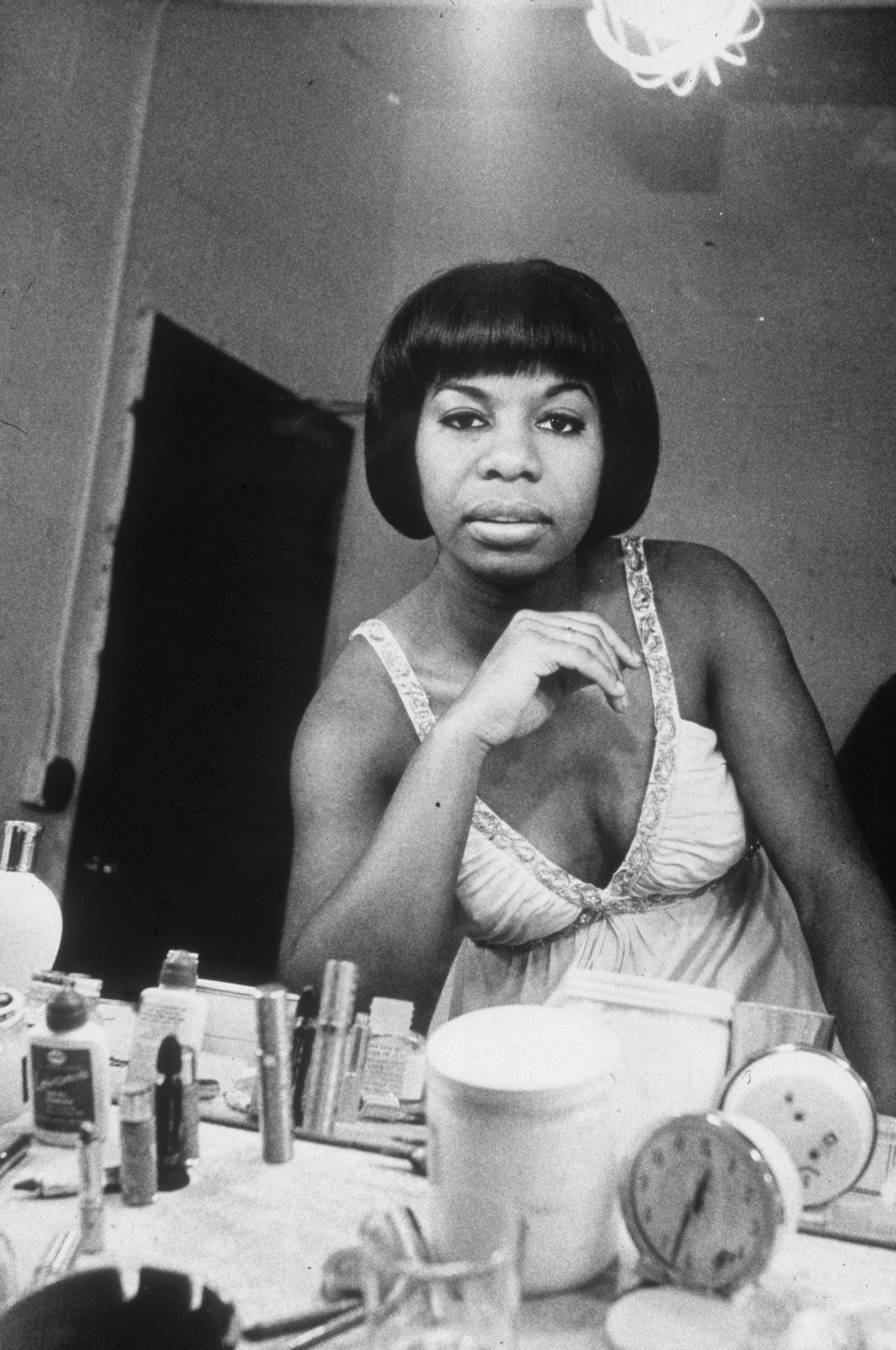 19th March 1955:  Headshot of American singer and musician Nina Simone (1933 - 2003) seen in her dressing room mirror, seated at her makeup table at the Village Vanguard, before a live recording session, New York City.  (Photo by Sam Falk/New York Times Co./Getty Images)