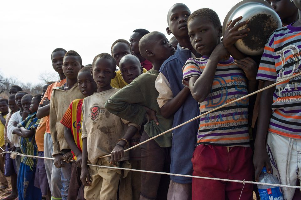 South Sudanese children wait for a food delivery at a refugee camp in Uganda. Hundreds of thousands of...