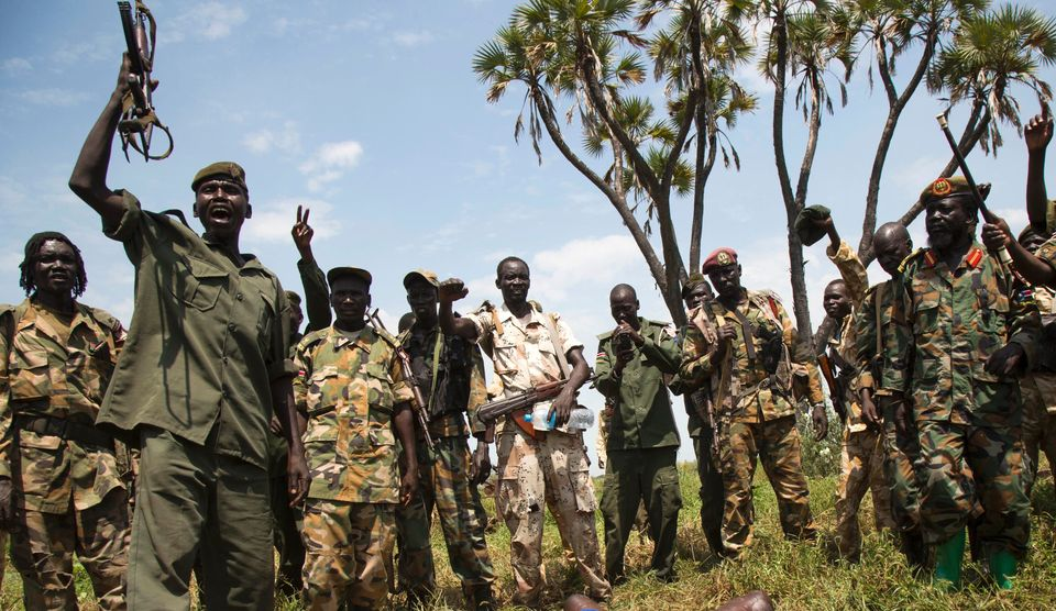 South Sudanese soldiers celebrate over the corpse of a rebel fighter. Government troops are...