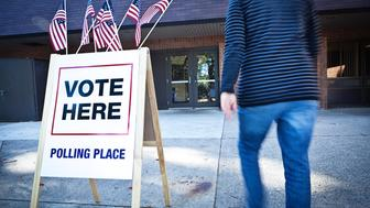 Unidentifiable woman voter entering a voting polling place for USA government election. Rear view shows her walking briskly in blurred motion by a sign decorated with American flags. For concepts of one person one vote, voter registration, voting booths, presidential and legistlative national and local decisions, democracy, and civic responsibility.