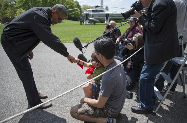 Obama fist bumps with 4-year-old Luca Martinez as he departs the White House in Washington, D.C., May...
