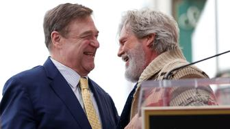 Actor John Goodman (L) embraces actor Jeff Bridges before unveiling his star on the Hollywood Walk of Fame in Los Angeles, California U.S., March 10, 2017. REUTERS/Mario Anzuoni