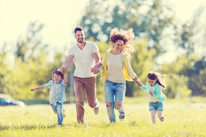 Happy young family running in the park and having fun. BraunS via Getty Images