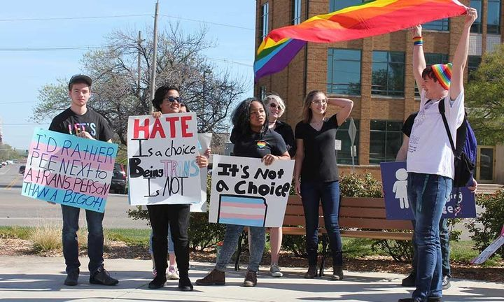 Six Kansas students hold signs supporting transgender rights. One is waving a large rainbow flag.