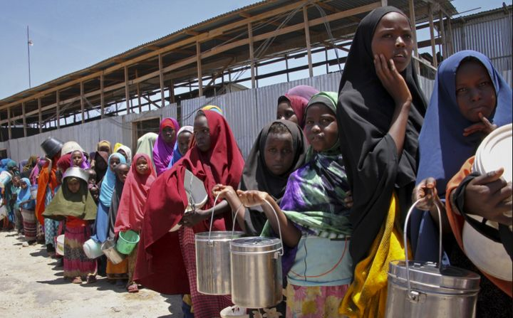 Somali girls standing in a queue to receive food handouts at a feeding center in  Mogadishu, Somalia.