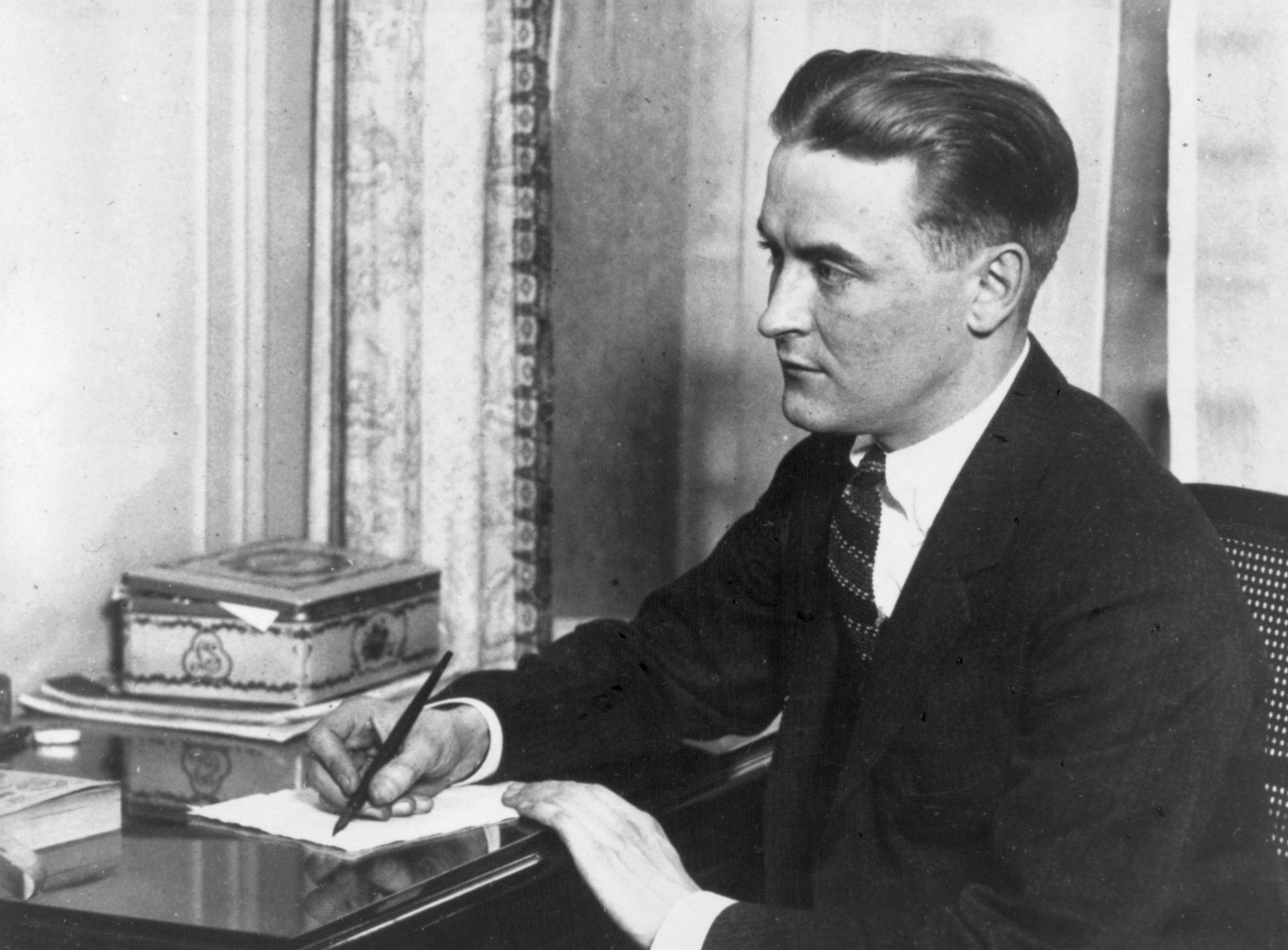 ORIGINAL CAPTION READS: Scott Fitzgerald (1896-1940), American writer.  Born in  St. Paul, Minnesota, and was an officer in World War I.  He was also a scriptwriter in Hollywood, and famed as a chronicler of the Jazz Age.  His Books included 'This Side of Paradise,' 'The Great Gatsby,' 'Tender is the Night,' and 'All the Sad Yound Men.'  He is shown here seated at a desk, writing with a pen.  Undated photograph.