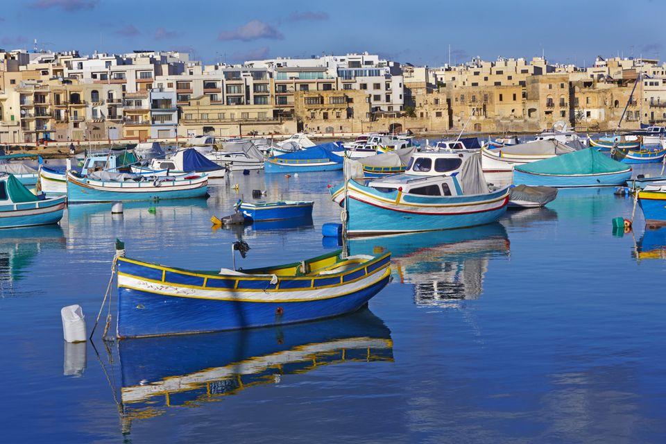Traditional colourful Maltese fishing boats in St George's bay against blue skies in Birzebugga, Malta.