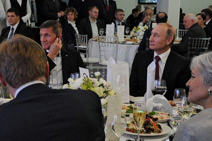 Retired Lt. Gen. Michael Flynn, left, sits with Russian President Vladimir Putin at an exhibition marking the 10th anniversar