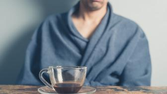 A tired young man wearing a bathrobe is sitting at a table and is trying to wake up by having a cup of coffee