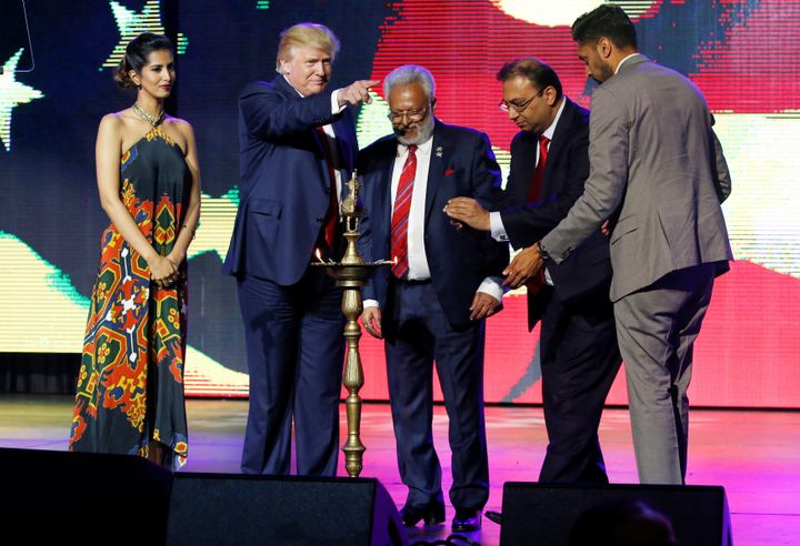 Republican Hindu Coalition Chairman Shalli Kumar (C) stands with Republican presidential nominee Donald Trump (2nd L) to ligh