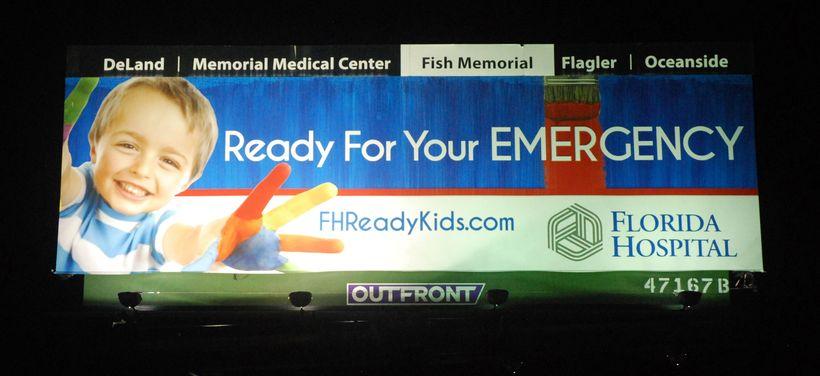 <em>Before: billboard lit by higher-wattage metal halide fixtures</em>