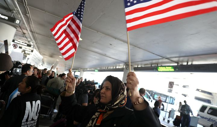 A protester waves American flags during a demonstration against the immigration ban that was imposed by U.S. President Donald