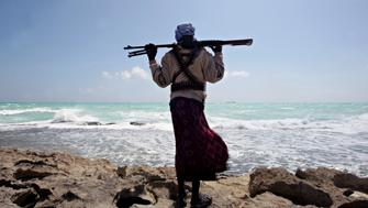 A file picture taken on January 7, 2010 shows an armed Somali pirate along the coastline while the Greek cargo ship, MV Filitsa, is seen anchored just off the shores of Hobyo town in northeastern Somalia where its being held by pirates. Attacks on the world's seas are soaring as armed and dangerous pirates become increasingly emboldened, seizing more ships than before and taking even bigger risks, an international body said on July 14, 2011. AFP PHOTO/ MOHAMED DAHIR (Photo credit should read MOHAMED DAHIR/AFP/Getty Images)