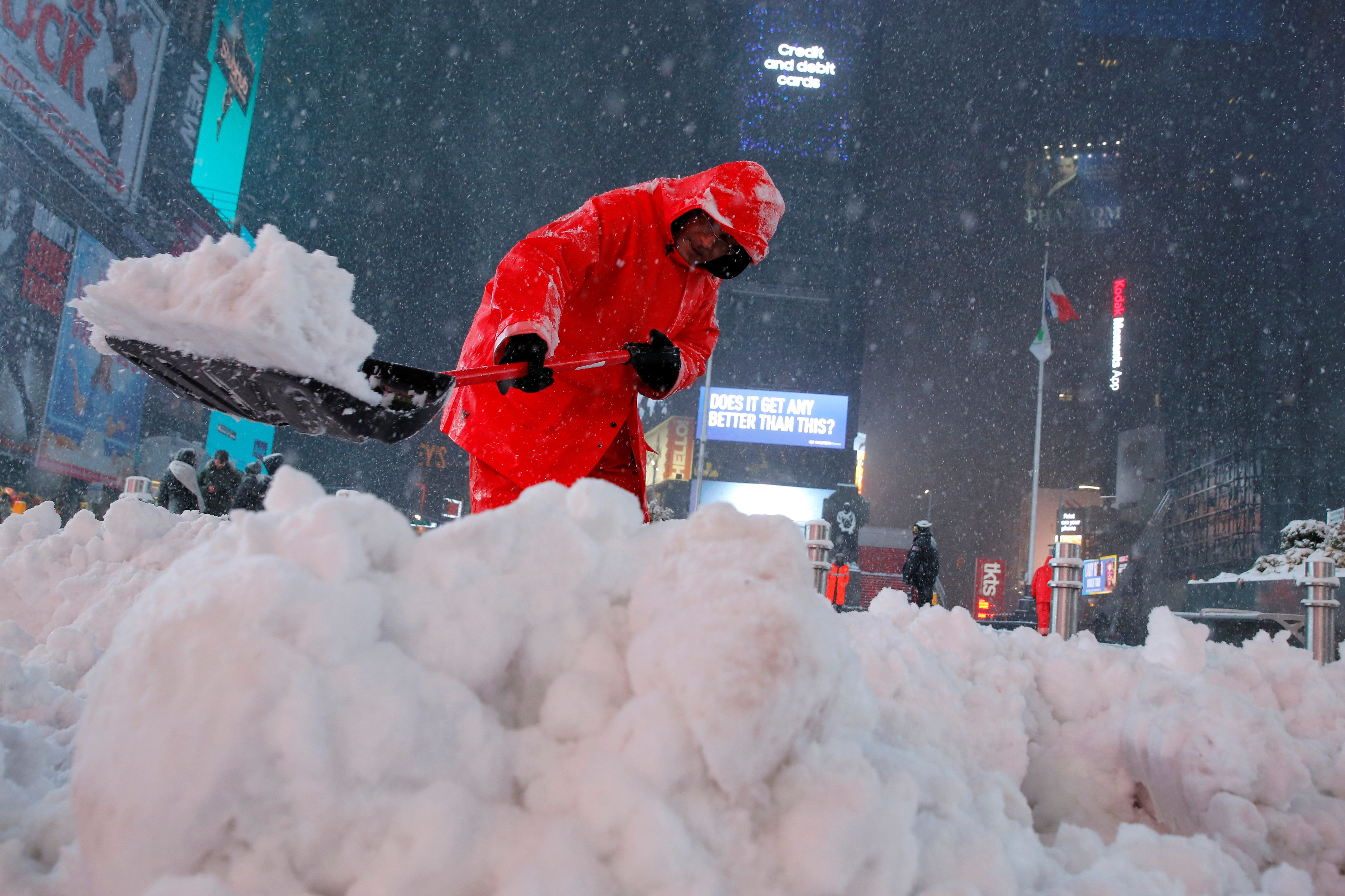 A worker clears snow in Times Square as snow falls in Manhattan, New York, U.S., March 14, 2017.  REUTERS/Andrew Kelly