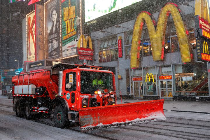 A snow plow drives through Times Square as snow falls in Manhattan on March 14, 2017.