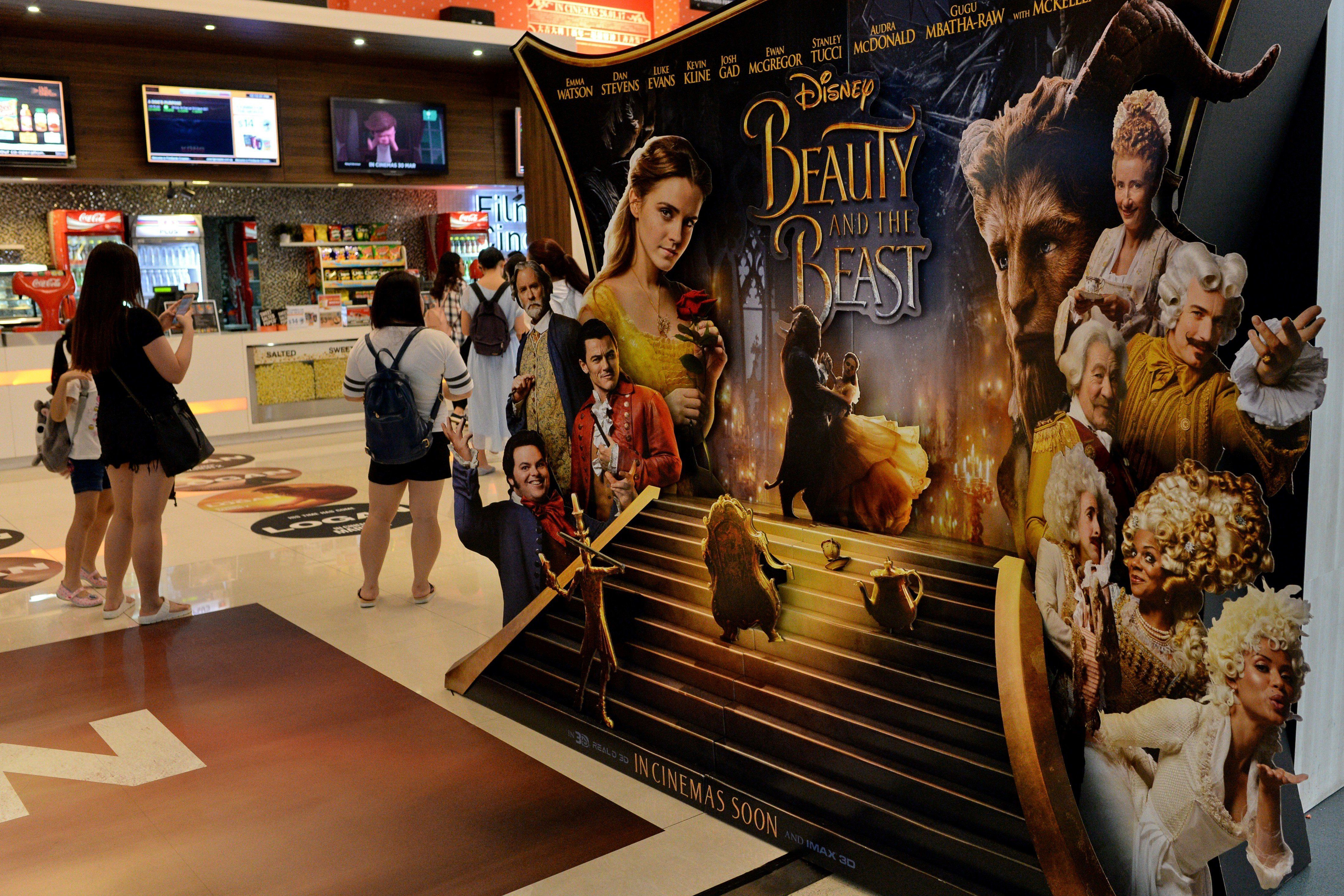 People stand near a promotional display for the film 'Beauty and the Beast' at a cinema in Singapore on March 14, 2017.  The film has come under fire from religious figures in Singapore, with Christian clergy attacking Disney for deviating from 'wholesome, mainstream values'. / AFP PHOTO / Roslan RAHMAN        (Photo credit should read ROSLAN RAHMAN/AFP/Getty Images)