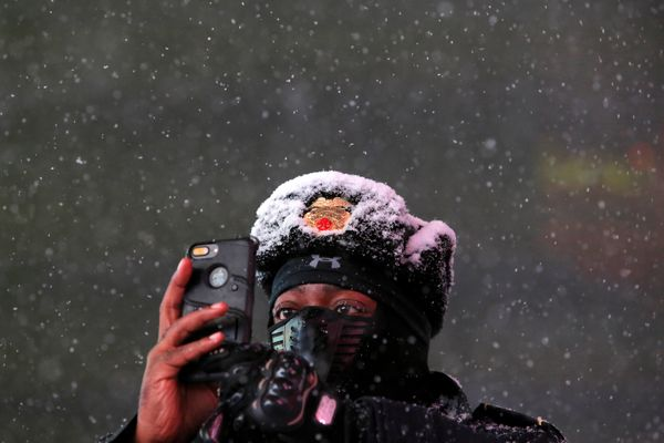 Times Square Public Safety Sergeant Baldwin Davis captures falling snow with his smartphone in Times Square, New York Ci