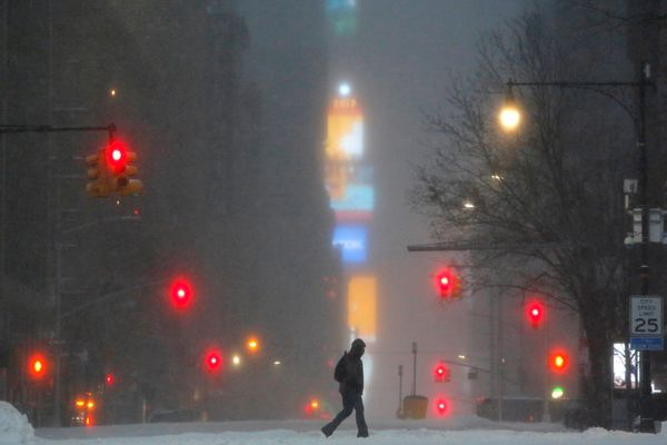 Times Square is obscured by the falling snow as a man walks along West 59th street in Manhattan, New York City, on March 14,