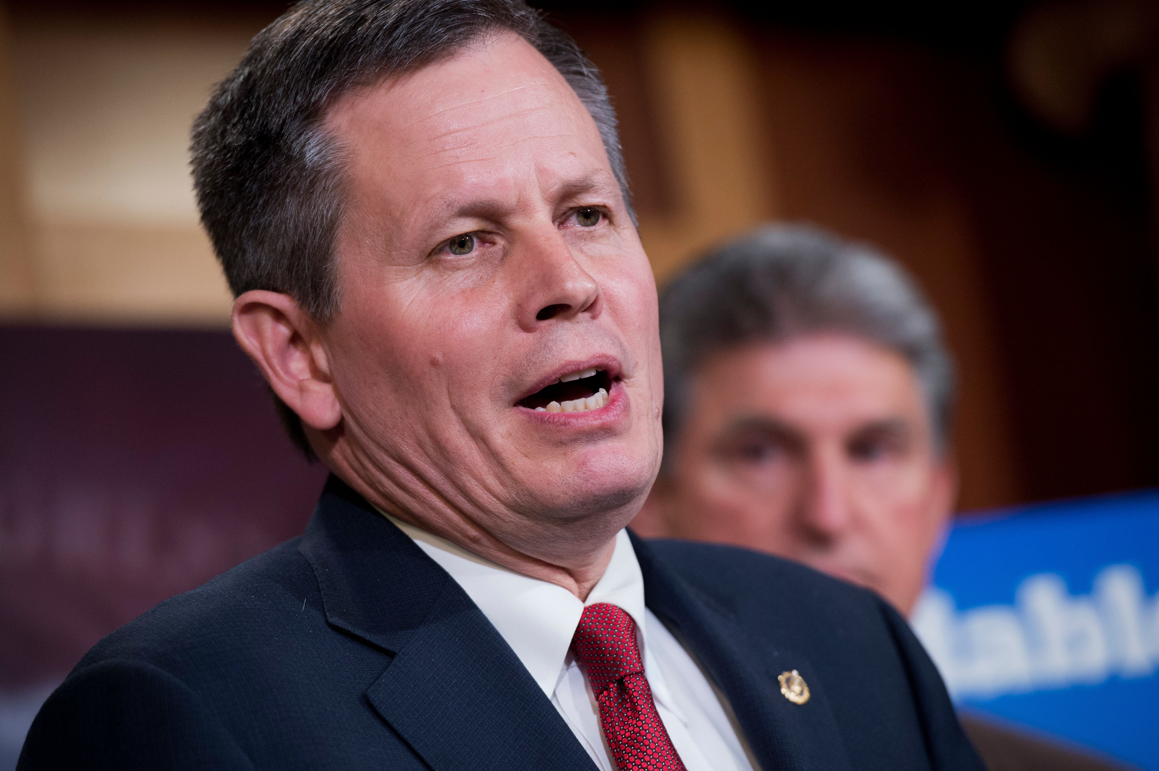 UNITED STATES - MAY 13: Sen. Steve Daines, R-Mont., speaks during a news conference in the Capitol's Senate studio to introduce greenhouse gas legislation that aims to 'rollback President Obama's Clean Power Plan,' May 13, 2015. Sen. Joe Manchin, D-W.Va., appears at right. (Photo By Tom Williams/CQ Roll Call)