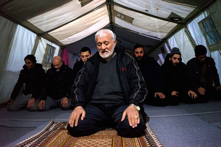 Imam Ali, a 68-year-old Palestinian refugee from Syria, leads prayers in the tented mosque at the Softex refugee camp outside
