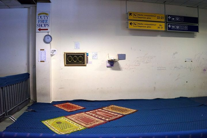 Prayer mats under the old Duty Free signs at the former Athens airport, now a refugee camp.