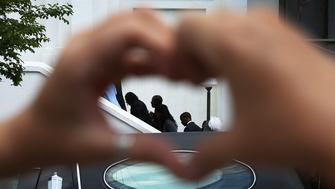 CHARLESTON, SC - JUNE 27:  Heather Hayward forms a heart with her hands as mourners file in for the funeral of Cynthia Hurd, 54, at the Emanuel African Methodist Episcopal Church where she was killed along with eight others in a mass shooting at the church on June 27, 2015 in Charleston, South Carolina. Suspected shooter Dylann Roof, 21 years old, is accused of killing nine people on June 17th during a prayer meeting in the church, which is one of the nation's oldest black churches in Charleston.    (Photo by Joe Raedle/Getty Images)