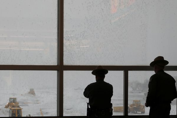 New York State Highway Patrol officers watch snow plows clear the runways at LaGuardia Airport in New York City on March