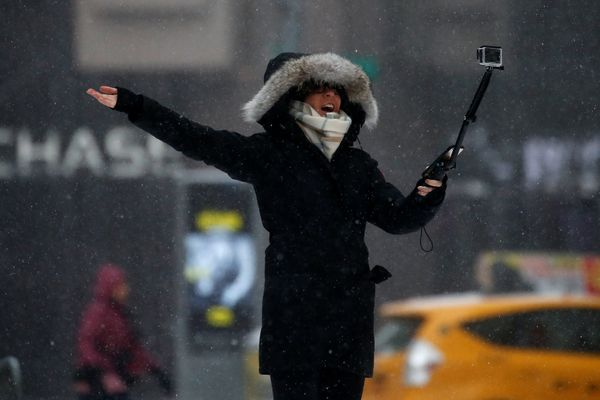 A bundled-up woman takes a selfie in Times Square, New York City, on March 14, 2017.