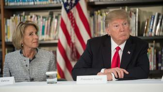 US President Donald Trump and Education Secretary Betsy DeVos listen during a meeting with parents and teachers at Saint Andrew Catholic School in Orlando, Florida, on March 3, 2017. / AFP PHOTO / NICHOLAS KAMM        (Photo credit should read NICHOLAS KAMM/AFP/Getty Images)