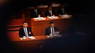 Chinese President Xi Jinping (L) and Premier Li Keqiang (C) attend the second plenary session of the National People's Congress, China's legislature, at the Great Hall of the People in Beijing on March 8, 2017. More than 3000 delegates from across China are attending the annual meeting of the country's rubber-stamp congress. / AFP PHOTO / FRED DUFOUR        (Photo credit should read FRED DUFOUR/AFP/Getty Images)