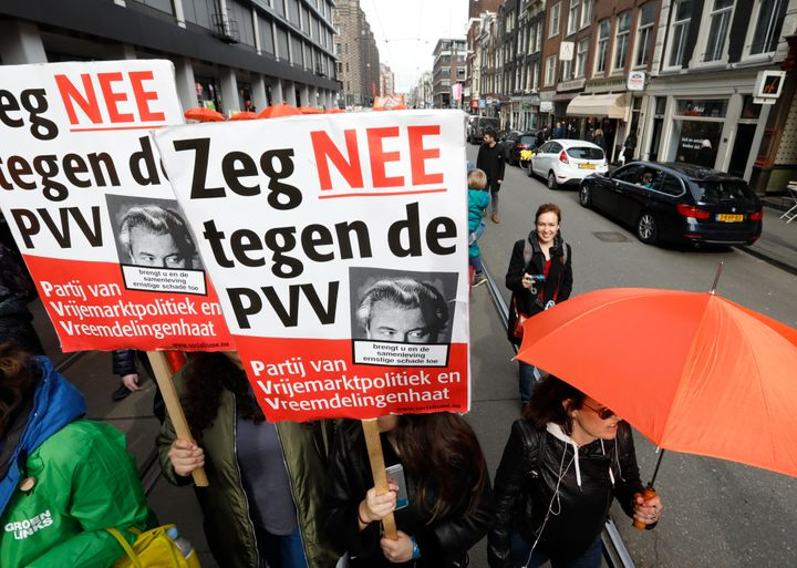 "Demonstrators carrying orange umbrellas and signs reading ""Say no to PVV"", march in Amsterdam on March 11."