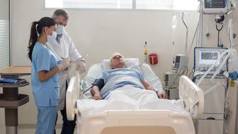 Doctors checking on a senior patient at the hospital€™s ICU - healthcare and medicine