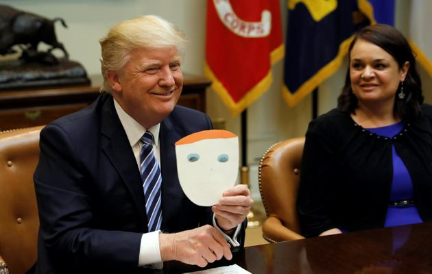 Trump, seen above holding a card made by a child and given to him by an attendee of a healthcare meeting,...