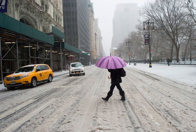 A woman makes her way across snowy streets in New York during Storm