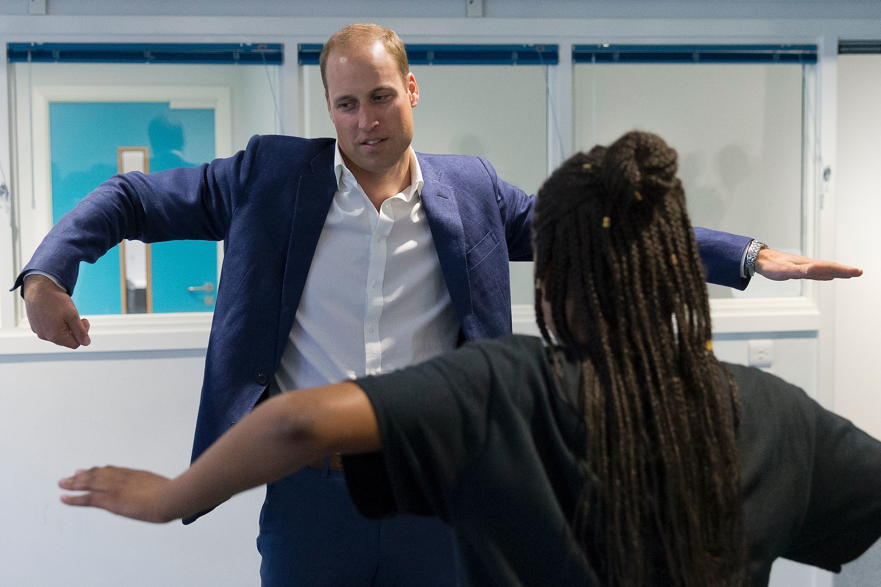 Prince William, Duke of Cambridge, learns a dance move with Scariofunk dance collective during a visit to Caius House Youth C