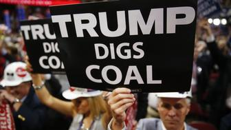 A delegate holds a sign reading 'Trump Digs Coal' during the Republican National Convention (RNC) in Cleveland, Ohio, U.S., on Wednesday, July 20, 2016. Donald Trump, a real-estate developer, TV personality, and political novice, was formally nominated as the 2016 Republican presidential candidate Tuesday night in Cleveland after his campaign and party officials quashed the remnants of a movement to block his ascension. Photographer: Andrew Harrer/Bloomberg via Getty Images