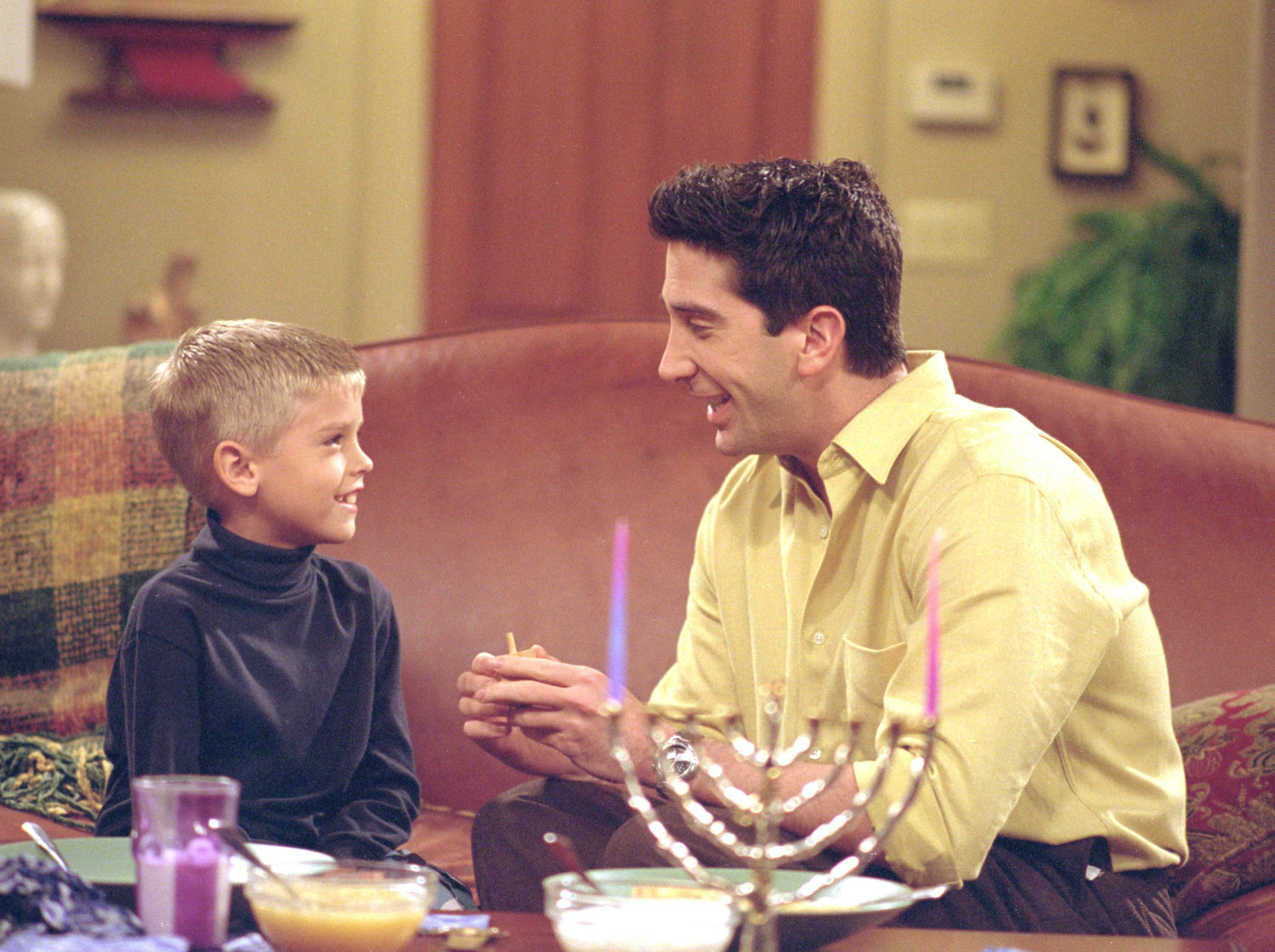 385848 23: Actors Cole Mitchell Sprouse (Big Daddy) as Ben and David Schwimmer as Ross Geller star in NBC's comedy series 'Friends' episode 'The One with the Holiday Armadillo.' Ross has Ben for the holidays and decides that this season, they will celebrate Chanukah instead of Christmas. (Photo by Warner Bros. Television)