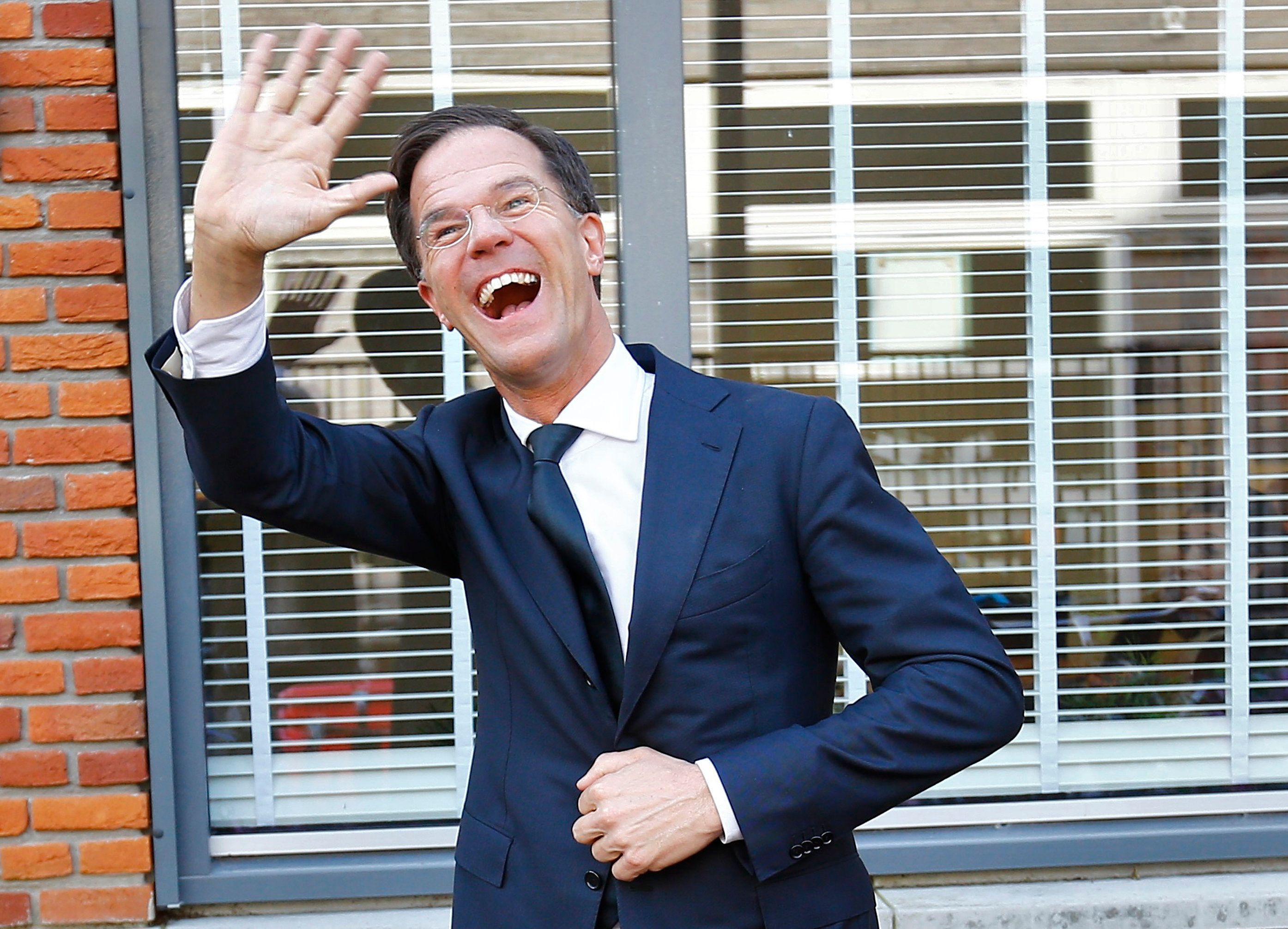 Dutch Prime Minister Mark Rutte of the VVD waves after voting in the general election.