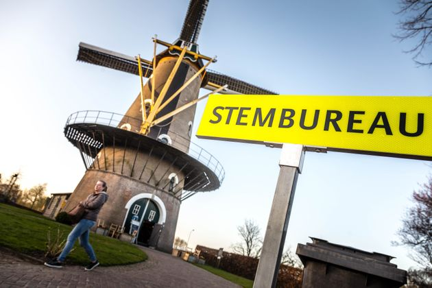A woman walks past a windmill as voters participate in the Dutch general
