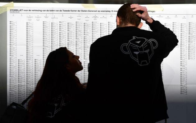 People stand in front of electoral lists as people vote in the Dutch general elections in The Hague on...