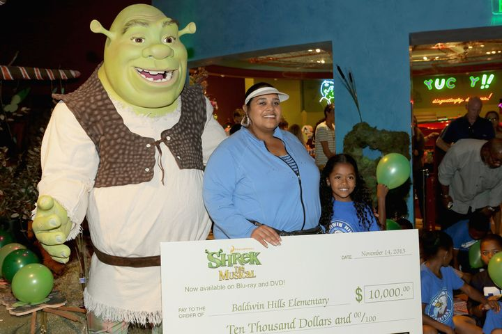 Williams accepted a $10,000 check from DreamWorks Animation and Twentieth Century Fox Home Entertainment for Baldwin Hills Elementary's arts program in 2013.