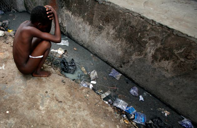A child squats by an open sewer in central Lagos. A 2016 WaterAid report finds almost 70...